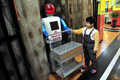A boy touches a robot that specialises