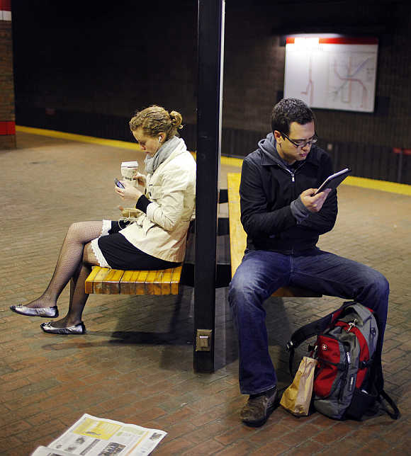A commuter reads on a Kindle e-reader while waiting in the subway in Cambridge, Massachusetts, United States.
