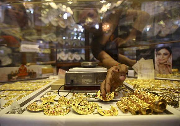 A store keeper arranges gold jewellery in Kathmandu.