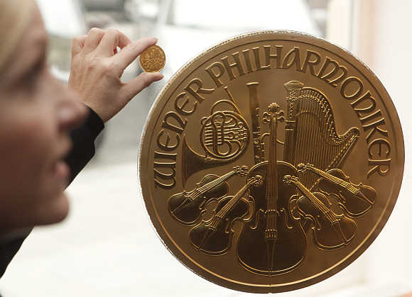 A woman displays a small gold coin next to Europe's largest gold