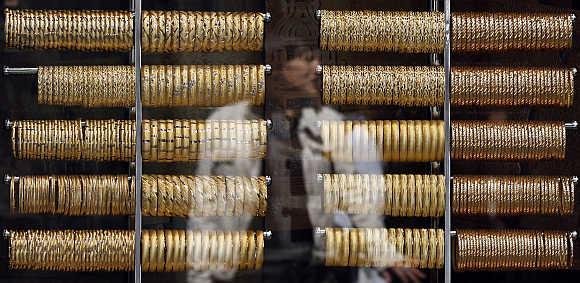 A woman is reflected on the window of a jewellery shop
