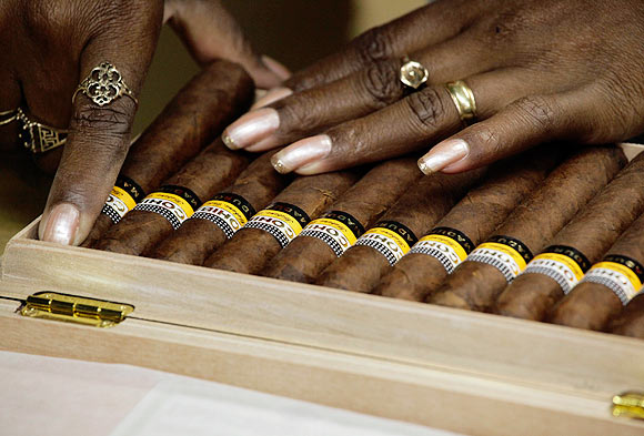 A worker fits Cohiba cigars in a box at the Partagas factory in Havana