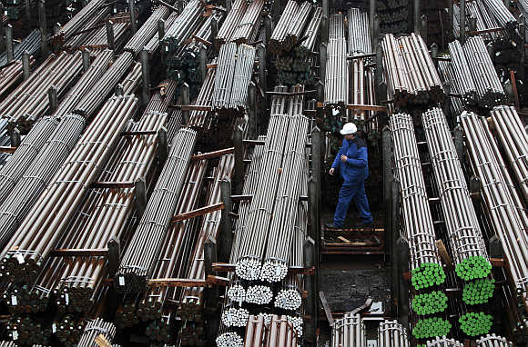 A workers walks through finished steel bars of different quality
