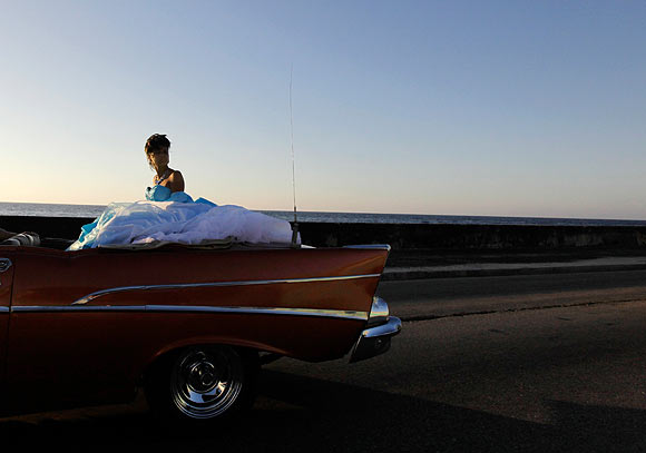 A young woman sits on the back of a convertible car