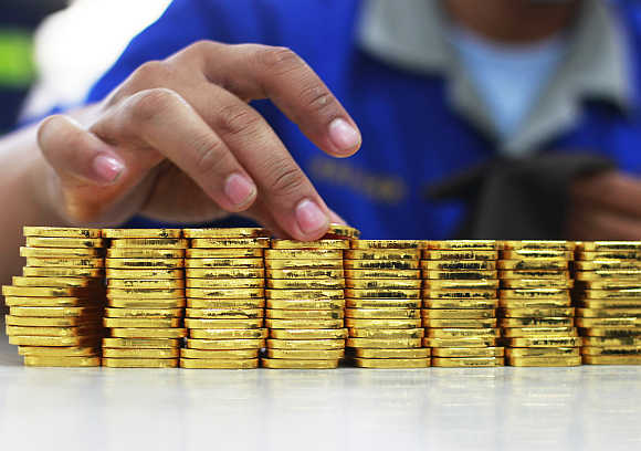 An employee holds a gold piece, each weighing 100 grams,