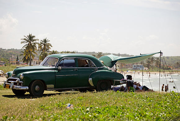 Cubans use a makeshift awning beside their car for shade