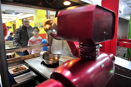 Customers watch a robot cooking dishes at a Robot Restaurant in Harbin, Heilongjiang province.