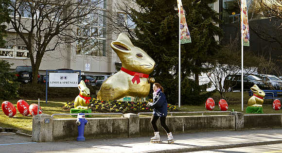 Giant gold-wrapped Easter bunnies are placed in front of the plant of Switzerland's