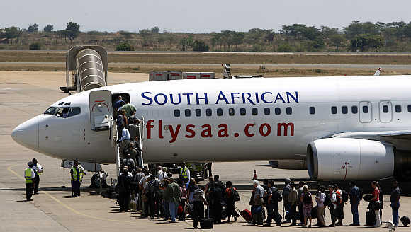 Passengers board a South African Airways Boeing 737 aircraft