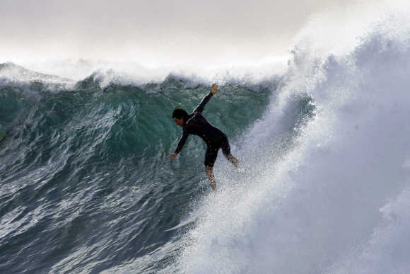 Surfer heads down the steep face of a wave at Sydney's