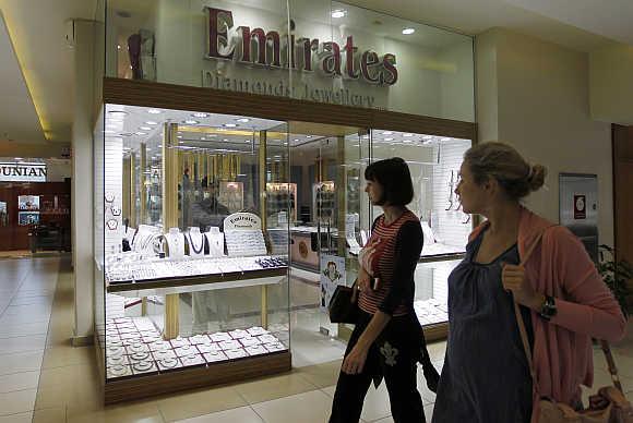 Women walk past the Emirates Diamonds shop at Gold and Diamond Park