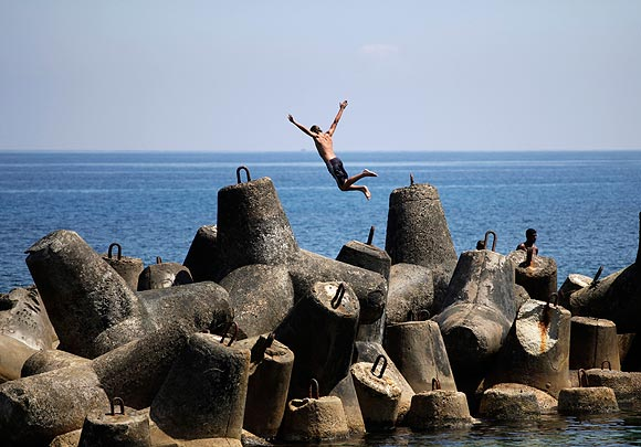 A youth jumps into the ocean from a breakwater in Havana.