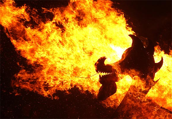 Flames engulf the dragon's head on a viking longboat