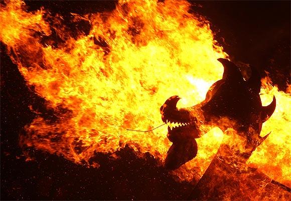Flames engulf the dragon's head on a viking longboat