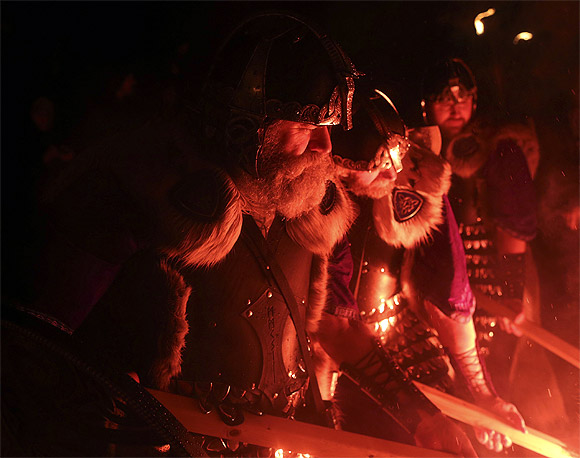 Jarl Squad vikings light up their torches during the Up Helly