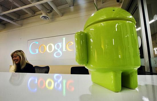 A Google Android figurine sits on the welcome desk as employee Tracy McNeilly smiles