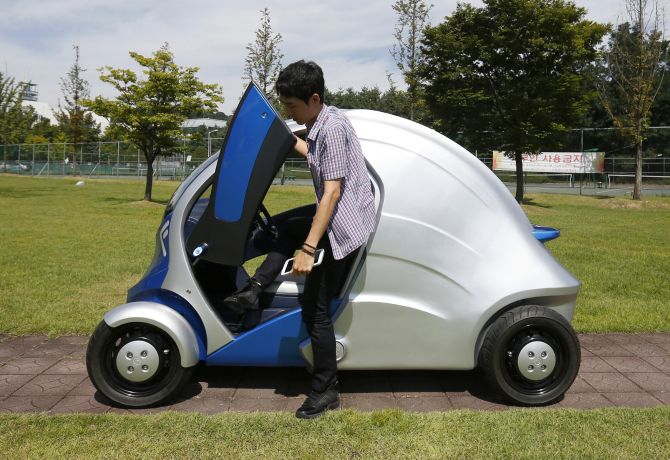 A researcher gets out of Armadillo-T, a foldable electric vehicle.